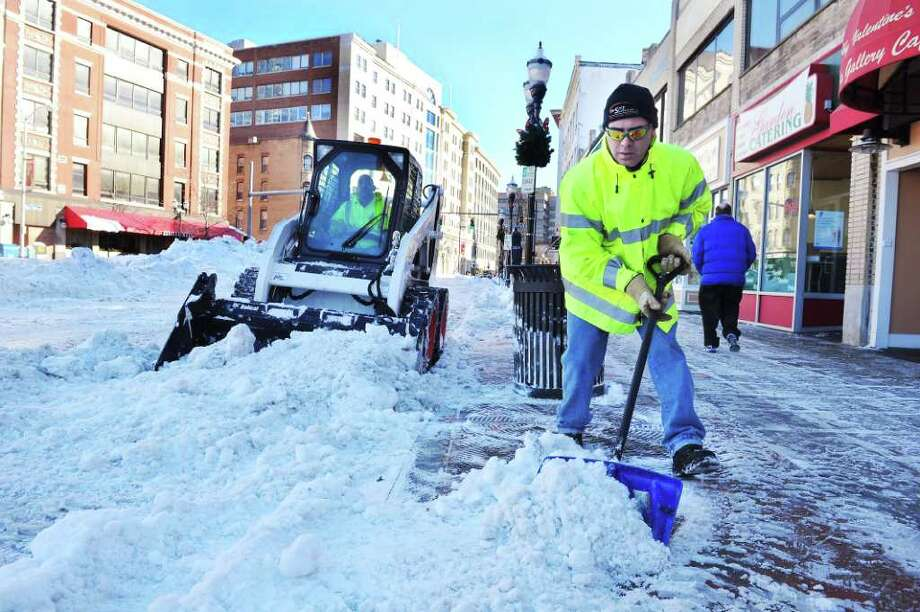 Ralph Vitti shovels the sidewalk as Stamford City of Operations crews remove snow from Wednesday's storm in Columbus Park in Stamford, Conn, on Thursday January 13, 2011.  Rob Loffredo operates the small plow. Photo: Kathleen O'Rourke / Stamford Advocate