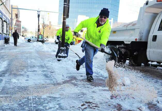 Bobby Gardner spreads sand along the sidewalk as Stamford City of Operations crews remove snow in Columbus Park in Stamford, Conn, on Wednesday January 13, 2011. Photo: Kathleen O'Rourke / Stamford Advocate
