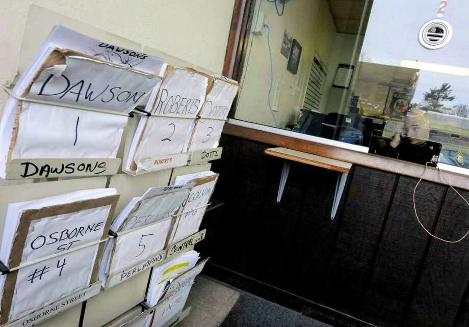 Albany Police investigator Bill Wilson mans the phone answering mostly questions about the city's snow emergency and towed vehicles  at Albany's Traffic Safety Building in Albany Thursday Jan. 13, 2011. Maps to the various tow operators the city contracts with are in a rack ,left. ( Michael P. Farrell/Times Union ) Photo: Michael P. Farrell