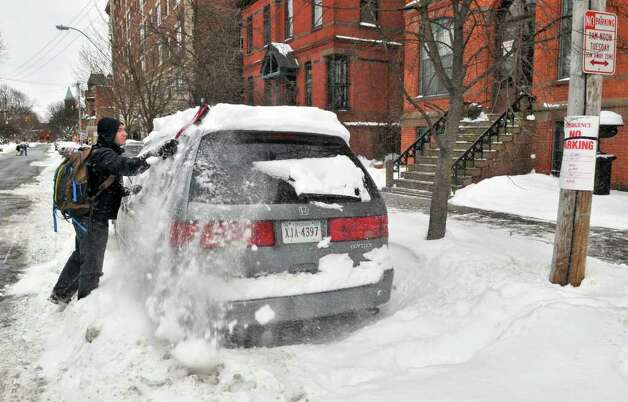 Jami Blair of Albany races to the clear snow and move his wife's van before it gets towed for being parked on the wrong side of Willet Street Thursday afternoon.  (John Carl D'Annibale / Times Union) Photo: John Carl D'Annibale