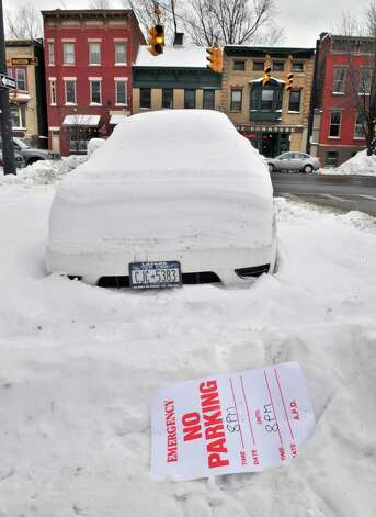 A snow-covered car parked in violation of Albany's snow emergency on Willet Street near the corner of Madison Ave. Thursday afternoon.  (John Carl D'Annibale / Times Union) Photo: John Carl D'Annibale