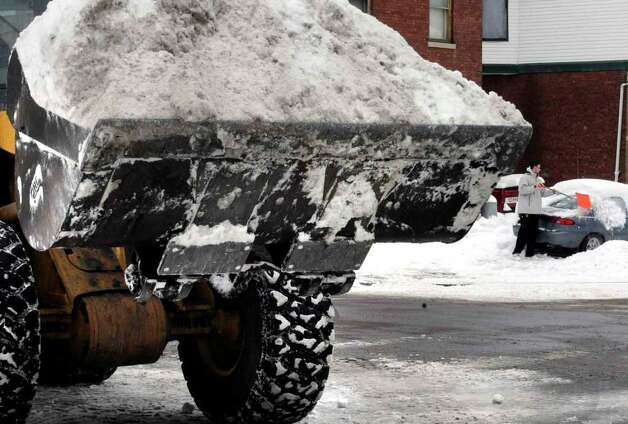 Brandon Brooks clears his car as a City of Schenectady bulldozer removes snow from the corner of Parkwood Boulevard and Rugby Road in Schenectady Thursday Jan. 13, 2011. ( Michael P. Farrell/Times Union ) Photo: Michael P. Farrell