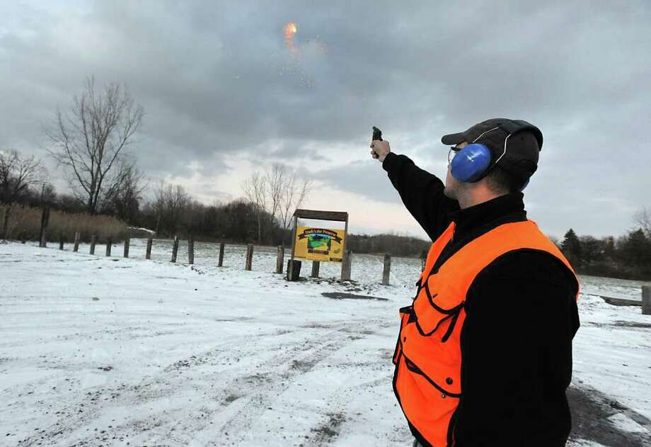 Bryan Haslun, a wildlife specialist from the U.S. Agriculture Department, uses pyrotechnics, loud noises and recorded calls of crows in distress, in a bid to drive away thousands of crows in Tivoli Lake Preserve in Albany, NY on December 16, 2010.  (Lori Van Buren / Times Union) Photo: Lori Van Buren