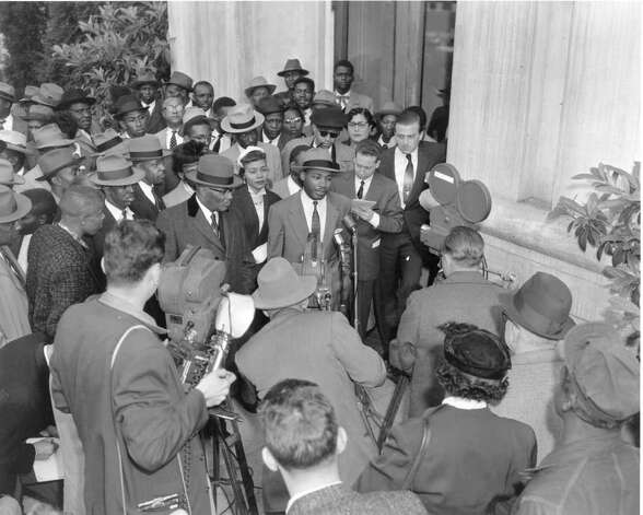 The Rev. Martin Luther King Jr., center, the first defendant called to trial in the racial bus boycott, held a press conference on March 19, 1956 on the steps of the Montgomery County courthouse where he and 92 others are on trial. They are charged with the violation of the anti-boycott law. King's wife, Coretta is by his side.  (AP Photo/Gene Herrick) Photo: GENE HERRICK, STF / Beaumont