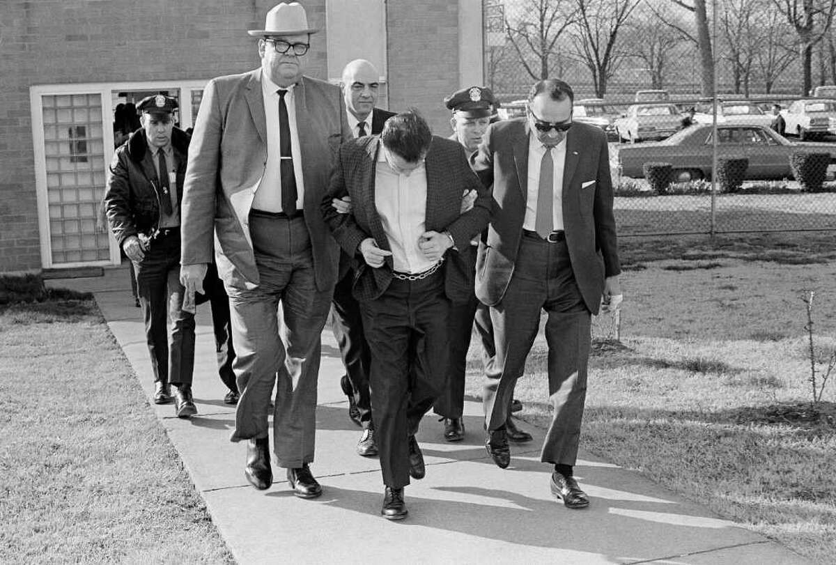 James Earl Ray lowers his head as State Safety Commissioner Greg O'Rear, white hat, and Highway Patrol Maj. Mickey McGuire, dark glasses, lead him to prison in Nashville, Tenn., March 11, 1969. Ray is serving a 99-year sentence in the death of Dr. Martin Luther King, Jr. in Memphis. (AP Photo)