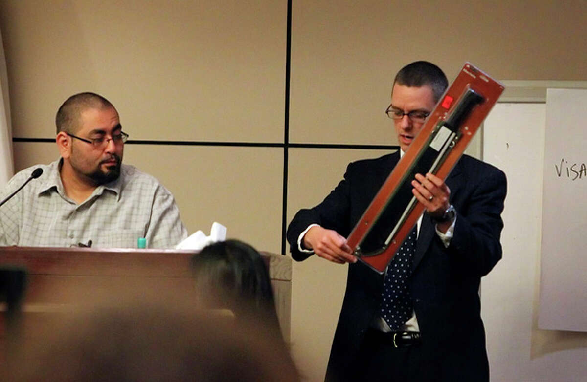 Bexar country prosecutor Christian Henricksen (right) holds an example of a machete that was purchased from a Southside Wal-Mart during the questioning of Wal-Mart employee Ruben Naranjo in the murder trial of Thomas Ahrens on Jan. 13.