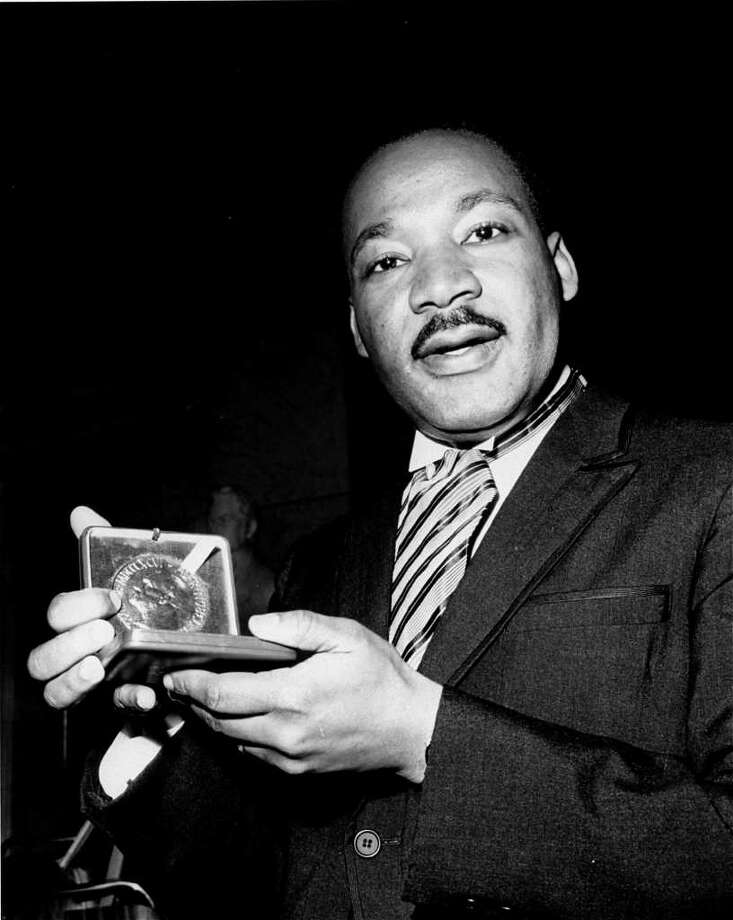 Dr. Martin Luther King, Jr. displays his 1964 Nobel Peace Prize medal in Oslo, Norway, December 10, 1964.  The 35-year-old Dr. King was honored for promoting the principle of non-violence in the civil rights movement.  (AP Photo) Photo: AP / AP