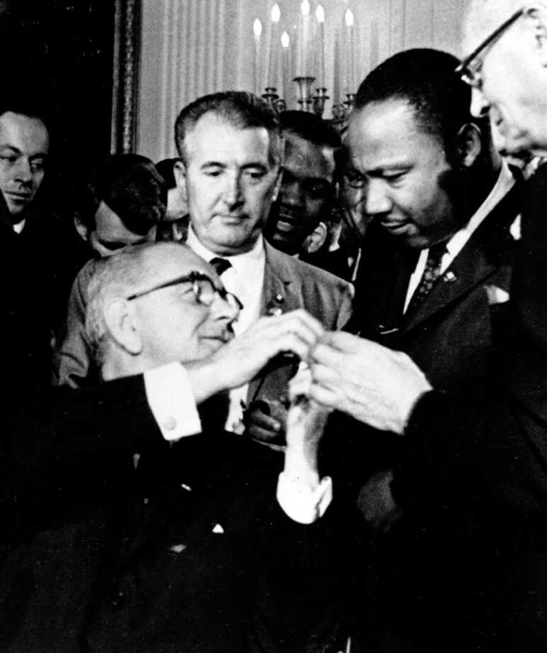 President Lyndon B. Johnson reaches to shake hands with Dr. Martin Luther King Jr. after presenting the civil rights leader with one of the 72 pens used to sign the Civil Rights Act of 1964 in Washington, D.C., on July 2, 1964.  President Johnson asked for civil rights leader public support of his policies on Vietnam in tape recorded conversations released Friday, April 12, 2002, by Johnson's presidential library in Austin, Texas. (AP Photo) Photo: En, AP / AP
