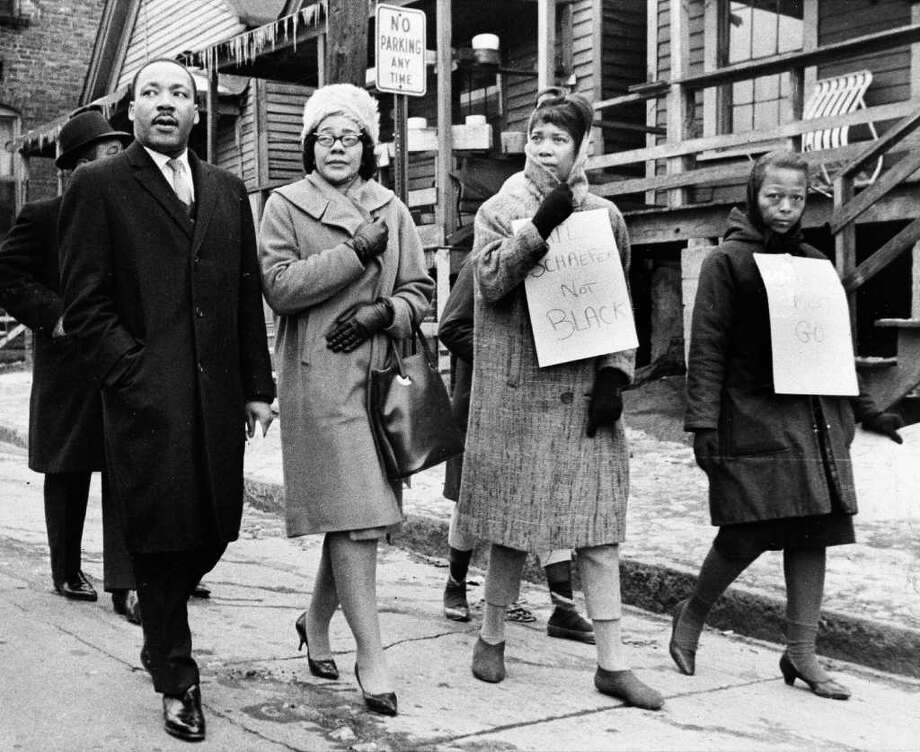 Dr. Martin Luther King, Jr., left, and his wife, Coretta Scott King, second from left, join pickets during a tour of an Atlanta slum area, in this Feb. 1, 1966 file photo.  The two women carrying signs were protesting the arrest of Hector Black, a volunteer who was charged with trespassing while handing out blankets at an apartment in the area. Coretta Scott King, who turned a life shattered by her husband's assassination into one devoted to enshrining his legacy of human rights and equality, has died, former mayor Andrew Young told NBC Tuesday morning, Jan. 31, 2006. She was 78. (AP Photo) Photo: AP