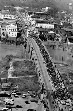 ** FILE ** Civil rights marchers cross the Alabama river on the Edmund Pettus Bridge at Selma March 21, 1965, with Dr. Martin Luther King Jr. at the lead at the start of a five day, 50-mile march to the State Capitol of Montgomery for voter registration rights for blacks. The two leading Democratic candidates for the 2008 presidential nomination, Sen. Hillary Rodham Clinton, D-N.Y. and Sen. Barack Obama, D-Ill., are scheduled to give nearly simultaneous speeches behind church pulpits just half a block apart from each other in Selma, Ala., on Sunday, March 4, 2007, to commemorate the 42nd anniversary of the bloody civil rights march there that helped rollback segregation in the South. Photo: ASSOCIATED PRESS / AP