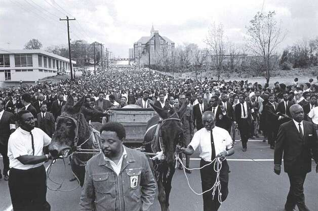 "This April 1968 photo released by the MLK Jr. National Historic Site, Martin Luther King Jr.s body is carried to Morehouse College in Atlanta, on a mule-drawn wagon accompanied by his aides dressed in denim attire. The wagon, mules and denim clothes symbolized the Poor Peoples Campaign. The  photograph is part of the  exhibition ""From Memphis to Atlanta: The Drum Major Returns Home"" at Atlanta's Martin Luther King, Jr. National Historic Site April 4-August 31, 2008. Photo: Bob Adelman, AP / MLK Jr. National Historic Site"