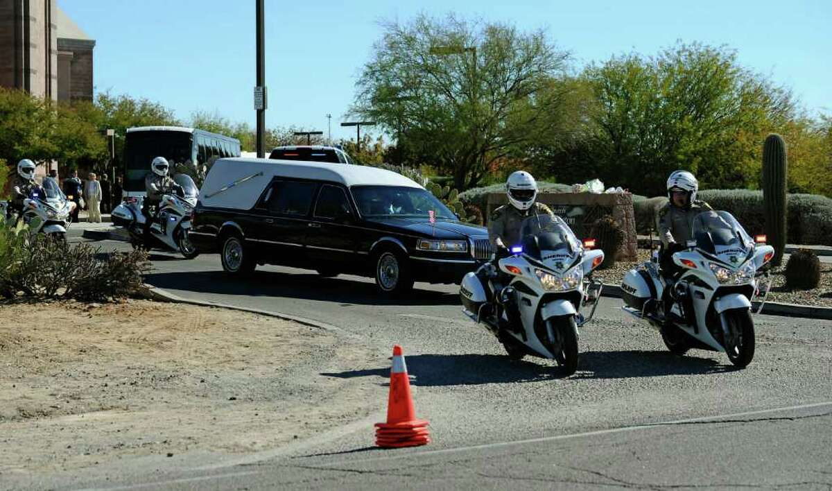 TUCSON, AZ - JANUARY 14: A hearse carrying the casket of US District Court Judge John Roll leaves St. Elizabeth Ann Seton church after a funeral service on January 14, 2011 in Tucson, Arizona. Heavy security surrounds the funeral of Judge Roll, who was shot during the January 8, shooting rampage of Jared Lee Loughner at a political event in Tucson, Arizona (Photo by Kevork Djansezian/Getty Images)