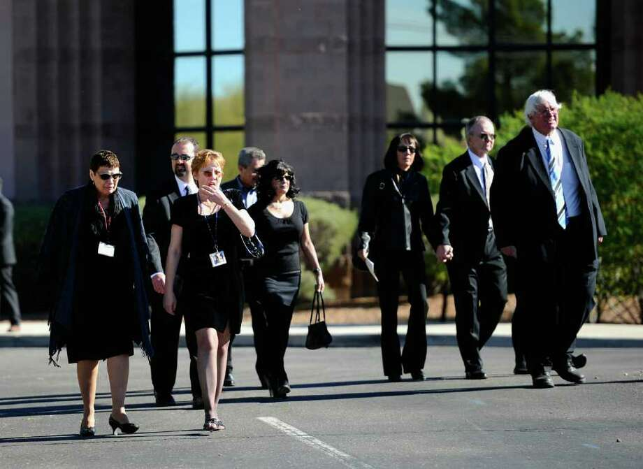 TUCSON, AZ - JANUARY 14:  Mourners leave St. Elizabeth Ann Seton church after funeral services for US District Court Judge John Roll January 14, 2011 in Tucson, Arizona. Heavy security surrounds the funeral of Judge Roll, who was shot during the January 8, shooting rampage of Jared Lee Loughner at a political event in Tucson, Arizona  (Photo by Kevork Djansezian/Getty Images) Photo: Kevork Djansezian