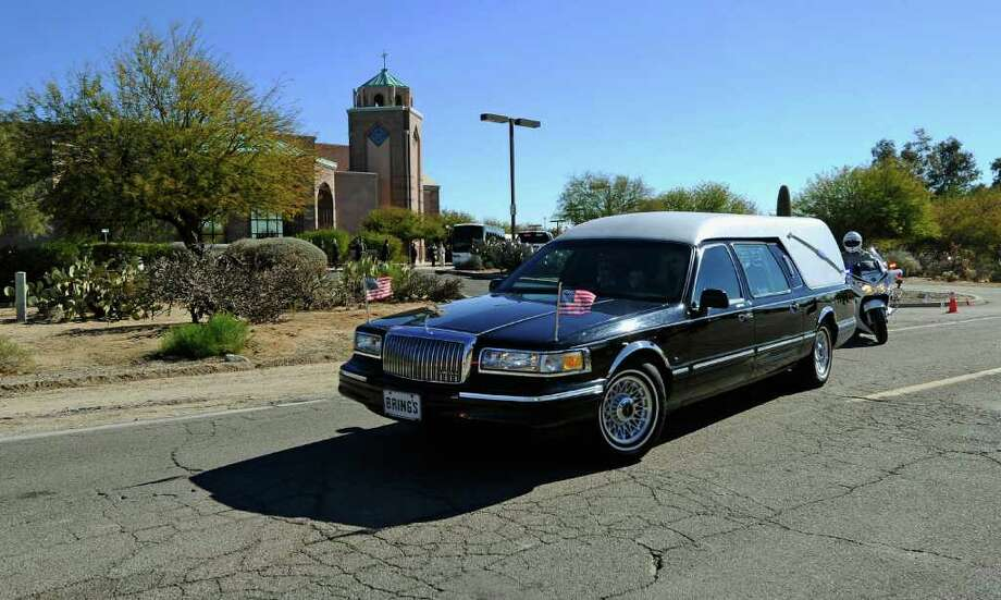 TUCSON, AZ - JANUARY 14:  A hearse carrying the casket of US District Court Judge John Roll leaves St. Elizabeth Ann Seton church after a funeral service on January 14, 2011 in Tucson, Arizona. Heavy security surrounds the funeral of Judge Roll, who was shot during the January 8, shooting rampage of Jared Lee Loughner at a political event in Tucson, Arizona  (Photo by Kevork Djansezian/Getty Images) Photo: Kevork Djansezian