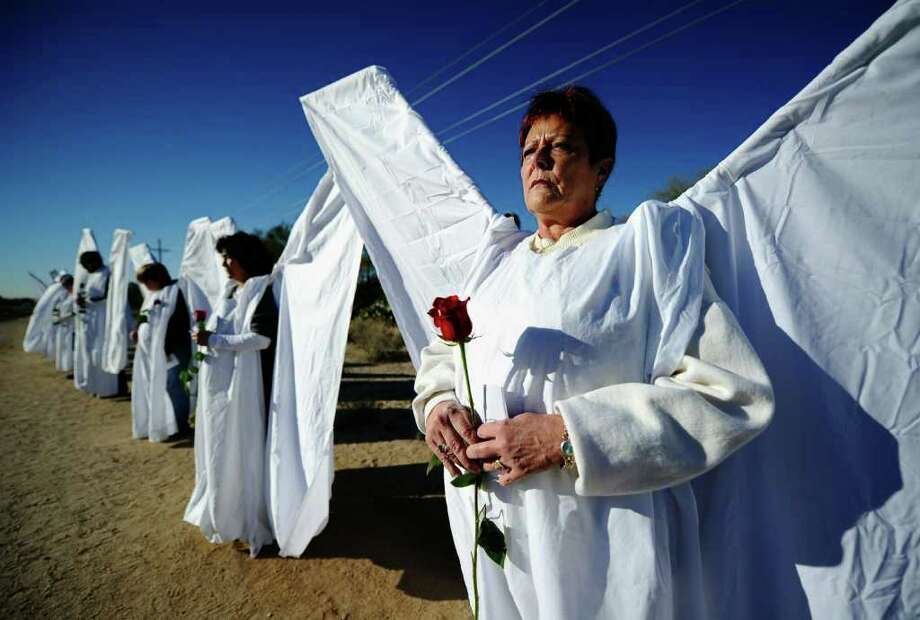 TUCSON, AZ - JANUARY 14:  People dressed as angels hold red roses and stand across the street from St. Elizabeth Ann Seton church where the funeral service for US District Court Judge John Roll is being held on January 14, 2011 in Tucson, Arizona. Heavy security surrounds the funeral of Judge Roll, who was shot during the January 8, shooting rampage of Jared Lee Loughner at a political event in Tucson, Arizona  (Photo by Kevork Djansezian/Getty Images) Photo: Kevork Djansezian