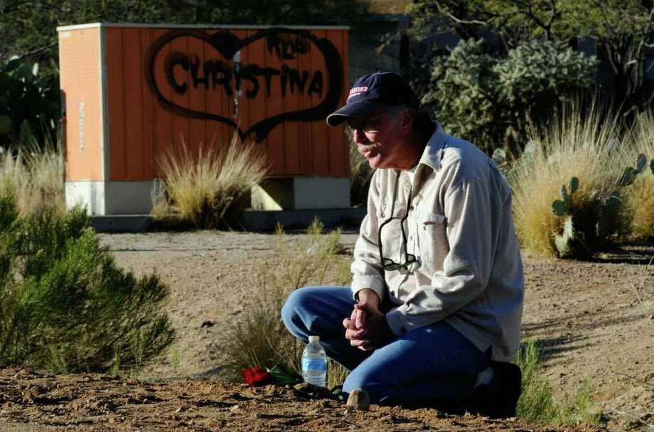 TUCSON, AZ - JANUARY 14:  Marty Kool kneels across the street from St. Elizabeth Ann Seton church where the funeral service for US District Court Judge John Roll is being held January 14, 2011 in Tucson, Arizona.  Heavy security surrounds the funeral of Judge Roll, who was shot during the January 8, shooting rampage of Jared Lee Loughner at a political event in Tucson, Arizona  (Photo by Kevork Djansezian/Getty Images) Photo: Kevork Djansezian