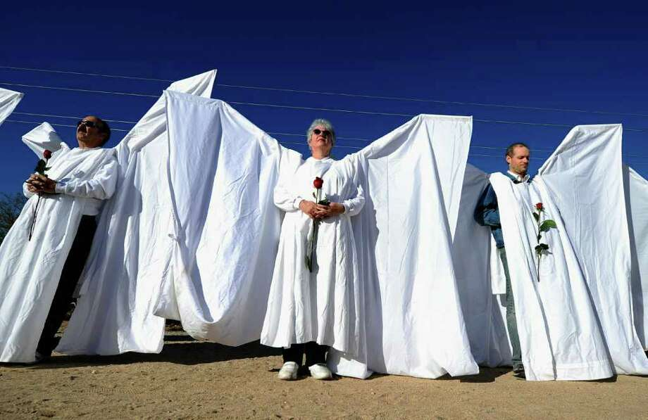TUCSON, AZ - JANUARY 14:  Mourners dressed as angels stand across the street from St. Elizabeth Ann Seton church where the funeral service for US District Court Judge John Roll is being held on January 14, 2011 in Tucson, Arizona. Heavy security surrounds the funeral of Judge Roll, who was shot during the January 8, shooting rampage of Jared Lee Loughner at a political event in Tucson, Arizona  (Photo by Kevork Djansezian/Getty Images) Photo: Kevork Djansezian