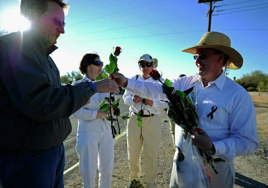 TUCSON, AZ - JANUARY 14:  Jay Stanforth passes out roses to mourners across the street from St. Elizabeth Ann Seton church where the funeral service for US District Court Judge John Roll is being held January 14, 2011 in Tucson, Arizona. Heavy security surrounds the funeral of Judge Roll, who was shot during the January 8, shooting rampage of Jared Lee Loughner at a political event in Tucson, Arizona  (Photo by Kevork Djansezian/Getty Images) Photo: Kevork Djansezian