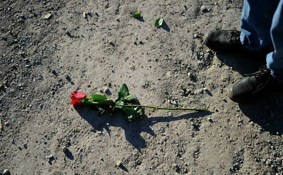 TUCSON, AZ - JANUARY 14:   A red rose lies on the street across from St. Elizabeth Ann Seton church during the funeral service for US District Court Judge John Roll on January 14, 2011 in Tucson, Arizona.Heavy security surrounds the funeral of Judge Roll, who was shot during the January 8, shooting rampage of Jared Lee Loughner at a political event in Tucson, Arizona  (Photo by Kevork Djansezian/Getty Images) Photo: Kevork Djansezian