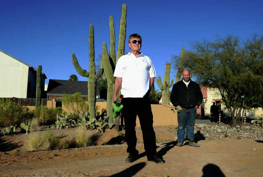 TUCSON, AZ - JANUARY 14:  Dennis Trump (L) and Craig Garver (R) stand across the street from St. Elizabeth Ann Seton church where the funeral service for US District Court Judge John Roll is being held on January 14, 2011 in Tucson, Arizona. Heavy security surrounds the funeral of Judge Roll, who was shot during the January 8, shooting rampage of Jared Lee Loughner at a political event in Tucson, Arizona  (Photo by Kevork Djansezian/Getty Images) Photo: Kevork Djansezian