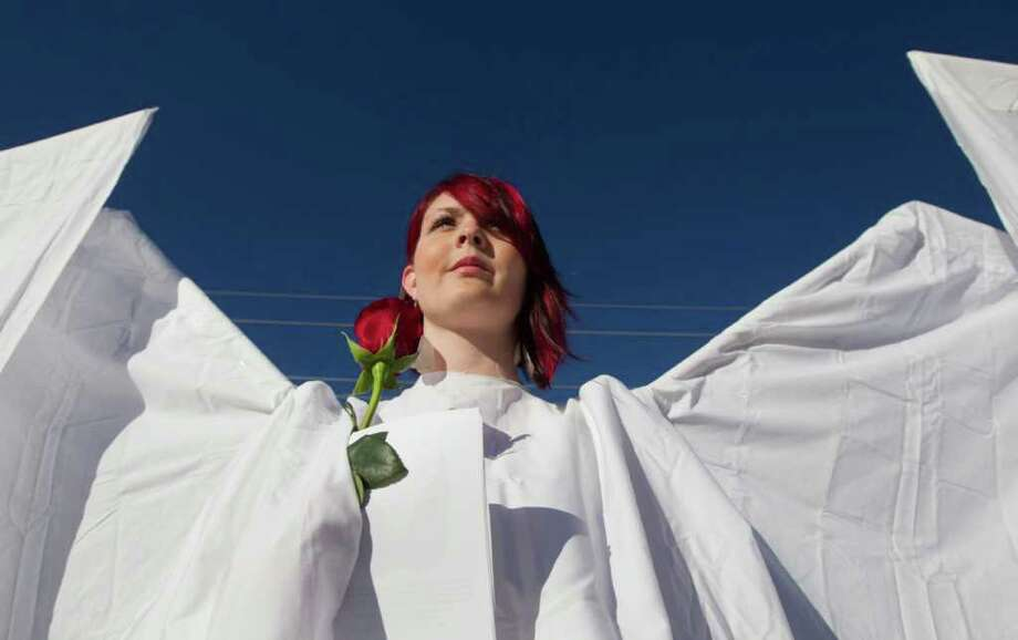Jessica Dewitt, of Phoenix, is dressed as an angel outside the St. Elizabeth Ann Seton Church for the funeral of U.S. District Judge John Roll on Friday, Jan. 14, 2011, in Tucson, Ariz. (AP Photo/Chris Carlson) Photo: Chris Carlson