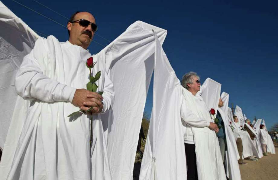 People dressed as angels line up outside the St. Elizabeth Ann Seton Church before the funeral of U.S. District Judge John Roll on Friday, Jan. 14, 2011, in Tucson, Ariz. (AP Photo/Chris Carlson) Photo: Chris Carlson