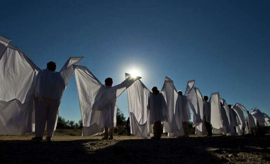 People dressed as angels stand outside the St. Elizabeth Ann Seton Church before the funeral of U.S. District Judge John Roll on Friday, Jan. 14, 2011, in Tucson, Ariz. (AP Photo/Chris Carlson) Photo: Chris Carlson