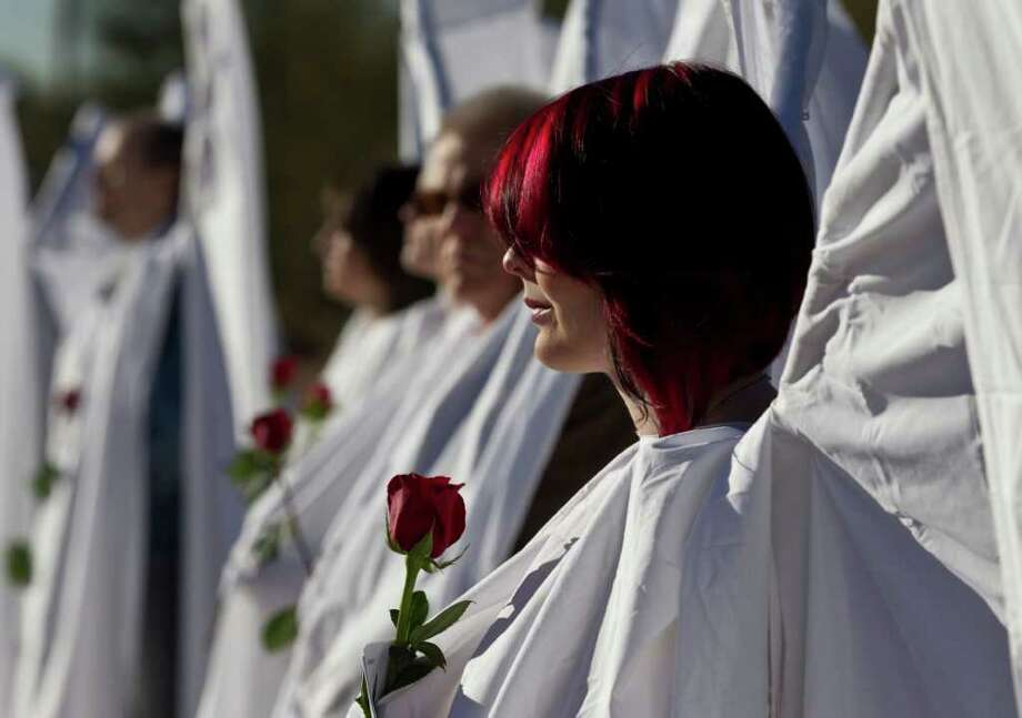 Jessica Dewitt of Phoenix is dressed as an angel outside the St. Elizabeth Ann Seton Church for the funeral of Judge John Roll Friday, Jan. 14, 2011, in Tucson, Ariz. (AP Photo/Chris Carlson) Photo: Chris Carlson
