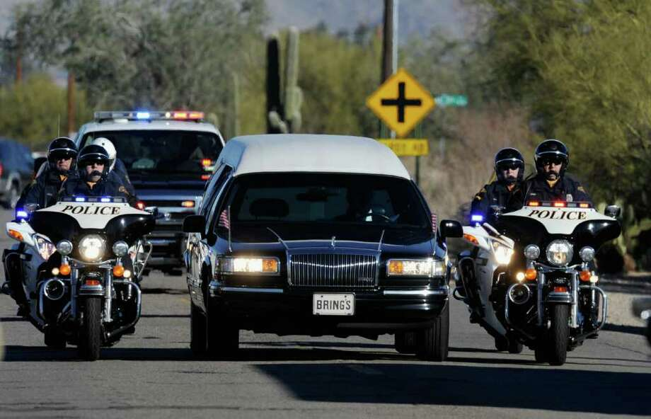 TUCSON, AZ - JANUARY 14:  The hearse carrying the casket of US District Court Judge John Roll passes in front of St. Elizabeth Ann Seton church on for a funeral service January 14, 2011 in Tucson, Arizona. Heavy security surrounds the funeral of Judge John Roll, who was shot during the January 8, shooting rampage of Jared Lee Loughner during a political event in Tucson, Arizona  (Photo by Kevork Djansezian/Getty Images) Photo: Kevork Djansezian