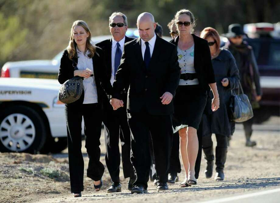 TUCSON, AZ - JANUARY 14:  Mourners arrive at the funeral service for US District Court Judge John Roll at St. Elizabeth Ann Seton church on January 14, 2011 in Tucson, Arizona.  Heavy security surrounds the funeral of Judge John Roll, who was shot during the January 8, shooting rampage of Jared Lee Loughner at a political event in Tucson, Arizona  (Photo by Kevork Djansezian/Getty Images) Photo: Kevork Djansezian