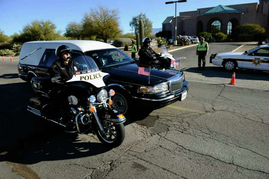 TUCSON, AZ - JANUARY 14:  A hearse carrying the casket of US District Court Judge John Roll passes i