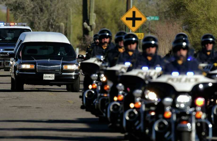 TUCSON, AZ - JANUARY 14:  A hearse carrying the casket of US District Court Judge John Roll passes in front of St. Elizabeth Ann Seton church for a funeral service January 14, 2011 in Tucson, Arizona. Heavy security surrounds the funeral of Judge Roll, who was shot during the January 8, shooting rampage of Jared Lee Loughner at a political event in Tucson, Arizona  (Photo by Kevork Djansezian/Getty Images) Photo: Kevork Djansezian