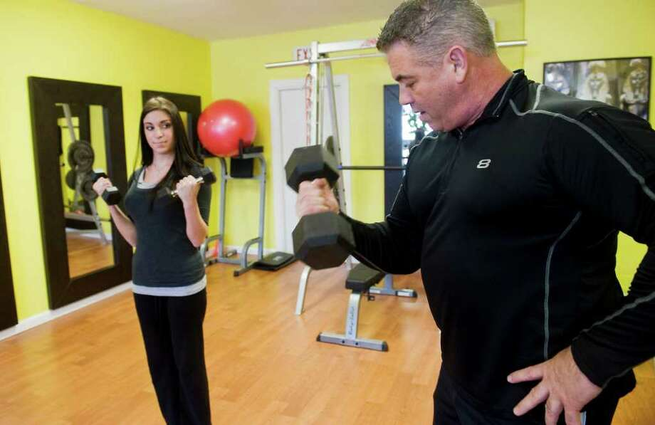 John Cleary, owner of Elite Training Concepts, works with client Elisabeth Arduini on proper bicep curls technique at their location in Darien, Conn, on Thursday December 30, 2010. (Hearst Newspapers) Photo: Kathleen O'Rourke / Stamford Advocate