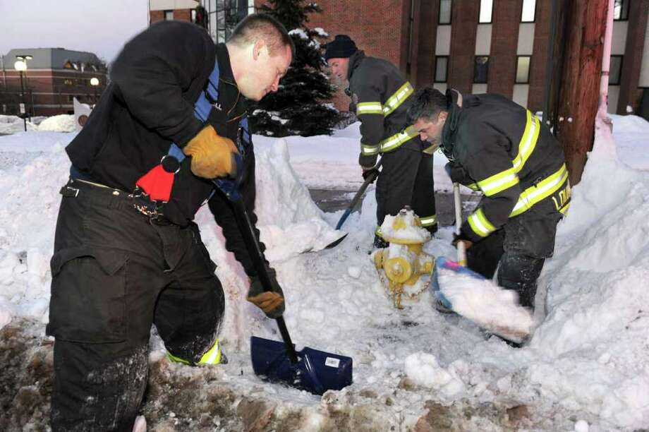 Danbury Firefighters from Engine 21, from left, Mike Jewell, Bill Ratajack and Lt. Bill Lounsbury, dig out a fire hydrant in front of City Hall in Danbury Friday afternoon. Photo taken January 14, 2011. Photo: Carol Kaliff / The News-Times