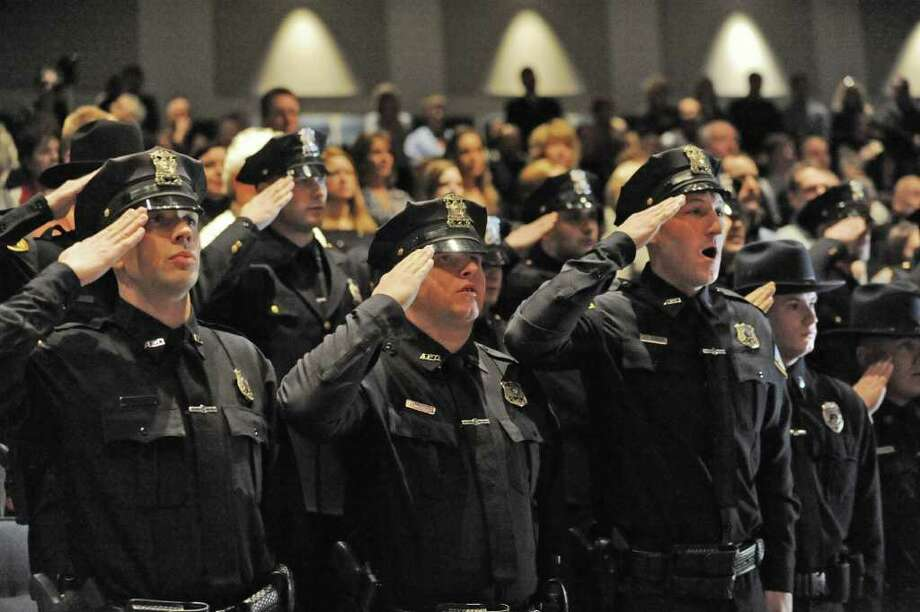 Zone Five Regional Law Enforcement Training Academy graduates stand for the Pledge of Allegiance at the beginning of a graduation ceremony at Schenectady Community College in Schenectady, NY on January 14, 2011. In front from left are, Officer Robert A. Caputo, Officer Joel D. Lochner and Officer Joseph E. Spencer, all of the Amsterdam Police Department. (Lori Van Buren / Times Union) Photo: Lori Van Buren