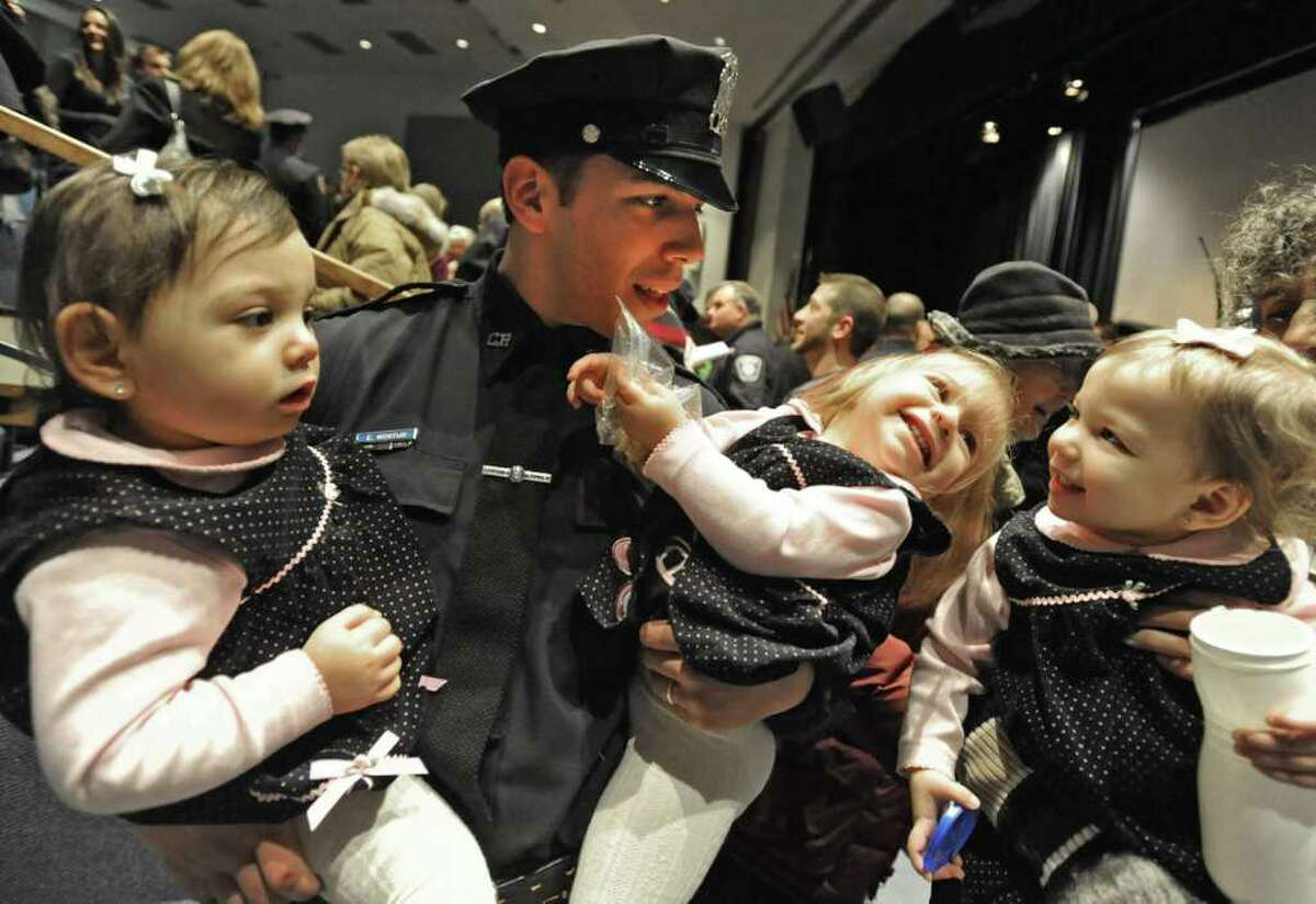 Officer Eric Montijo of Colonie gets hugs from his 20-month-old triplet daughters, from left, Chiara, Talia and Leah after a graduation ceremony at Schenectady Community College in Schenectady, NY on January 14, 2011. Officer Montijo is on the Colonie Police Department. His wife, Rebecca, is pregnant with two boys on the way. (Lori Van Buren / Times Union)