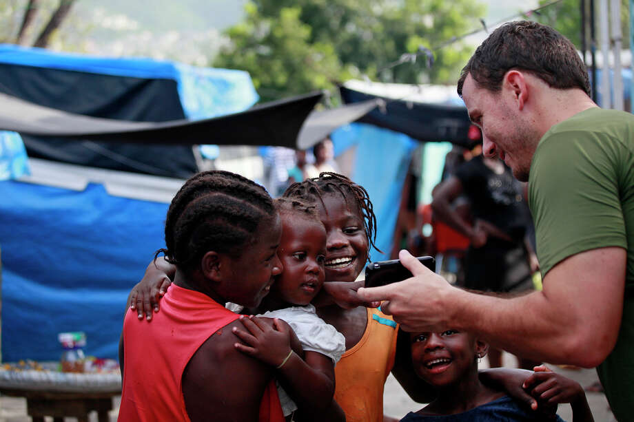 "Justin Yarborough shows girls a photograph he took of them in the tent city camp at the National Soccer Stadium in downtown Port-au-Prince where they were living last August. For Justin's 30th birthday, he created ""Project Thirty: $30 for 30 Days,"" during which he lived at the orphanage he supports and in the tent city. Photo: LISA KRANTZ/lkrantz@express-news.net / SAN ANTONIO EXPRESS-NEWS"