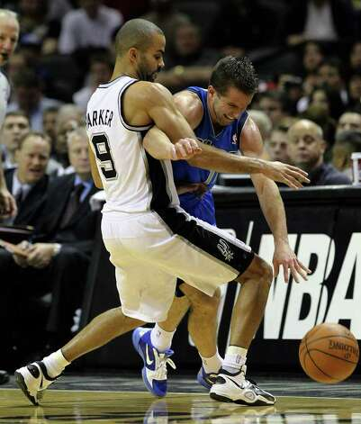 Spurs' Tony Parker (left) blocks Dallas Mavericks' Jose Barea in the second half at the AT&T Center on Friday, Jan. 14, 2011. Spurs defeated the Mavericks, 101-89. Kin Man Hui/kmhui@express-news.net Photo: KIN MAN HUI, SAN ANTONIO EXPRESS-NEWS / San Antonio Express-News