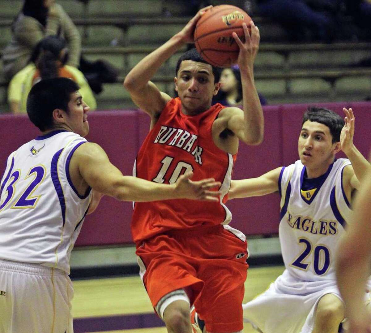 SPORTS Bulldog Jason Ainsworth moves into the lane between Jacob Gutierrez (32) and Jehu Ibanez as Burbank plays Brackenridge at Alamo Convocation Center on January 14, 2011. Tom Reel/Staff