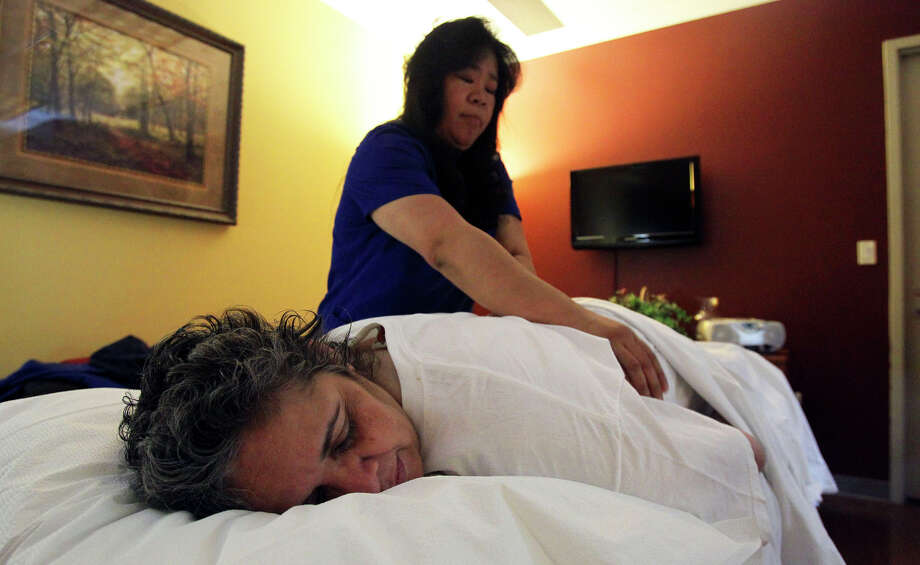 Lydia Galindo gets a complimentary massage at the Cancer Therapy & Research Center from massage therapist Michelle Anderson. Galindo, a cancer survivor, lives in El Paso and travels to San Antonio every six months for a checkup. Photo: JOHN DAVENPORT/jdavenport@express-news.net