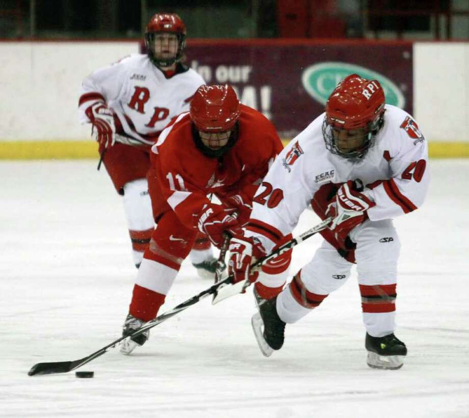 RPI?s Alisa Harrison, right, brings the puck up the ice against Cornell?s Brianne Jenner, center, during their game Friday. (Patrick Dodson/Special to the Times Union) Photo: Patrick Dodson / 10011736A