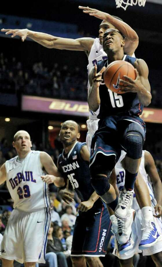 Connecticut's Kemba Walker, foreground, goes up for a shot against DePaul's Cleveland Melvin in the second half during an NCAA college basketball game in Rosemont, Ill., Saturday, Jan. 15, 2011. Connecticut won 82-62. (AP Photo/Paul Beaty) Photo: Paul Beaty, AP / Associated Press
