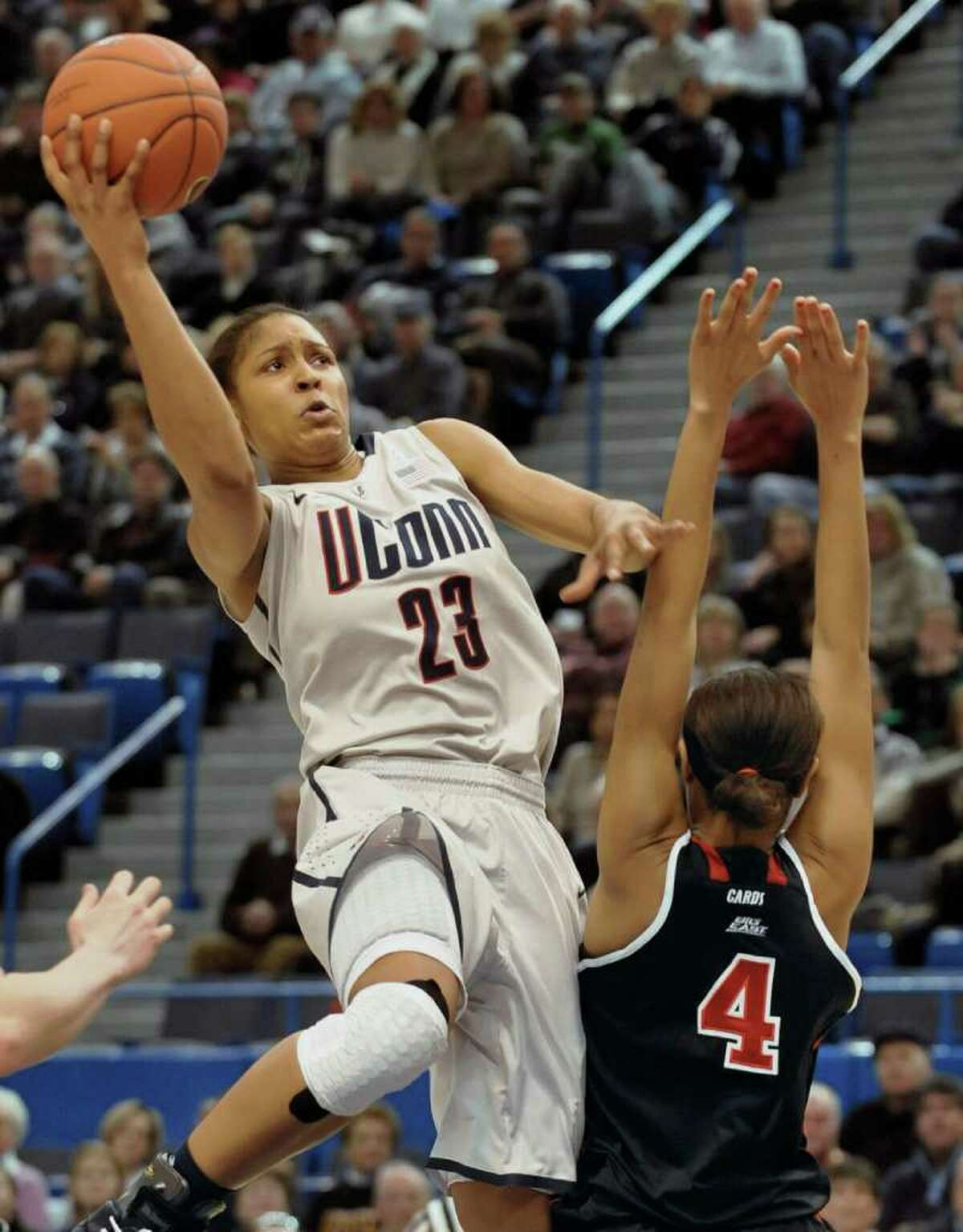 Connecticut's Maya Moore goes up for a basket while guarded by Louisville's Antonita Slaughter (4) during the first half of an NCAA college basketball game, in Hartford, Conn., Saturday, Jan. 15, 2011. (AP Photo/Jessica Hill)