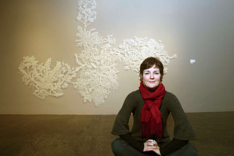 "Artist Leigh Anne Lester sits in front of ""Slowsidle,"" a large-scale cutout of a botanical amalgamate made with drafting film and countless X-acto blades. JOHN DAVENPORT / EXPRESS-NEWS"
