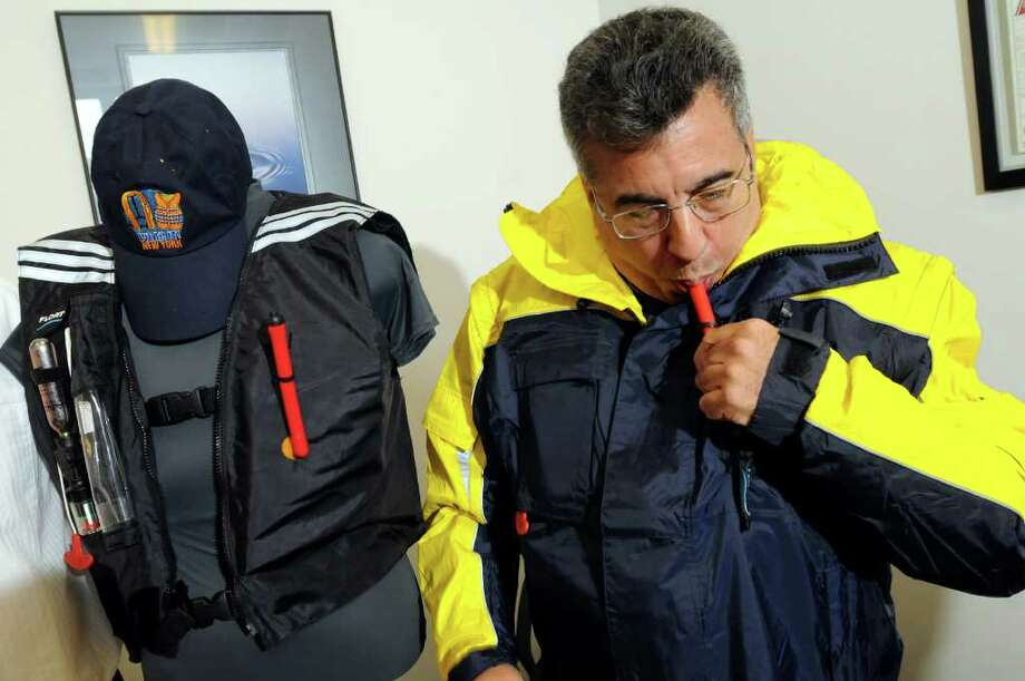 Sailor Ken Baer of Troy wears the Float-Tech device, which is zipped into the jacket, and demonstrates how he self-inflates the device on Tuesday, Jan. 11, 2011, at Float-Tech in Troy, N.Y. Baer says the inflating life preserver saved his life on the open sea. (Cindy Schultz / Times Union) Photo: Cindy Schultz