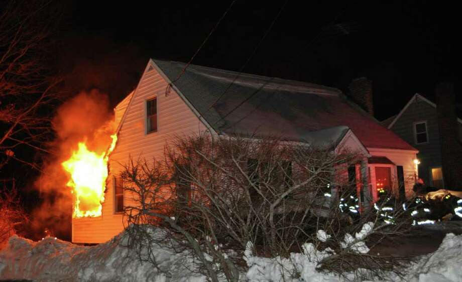 Firefighters rescued two dogs from a burning home Saturday night, but a family of four had to find shelter elsewhere as a fire swept through their 11 Senga Road house. Photo: Martha I. Escobar, CTPost.com