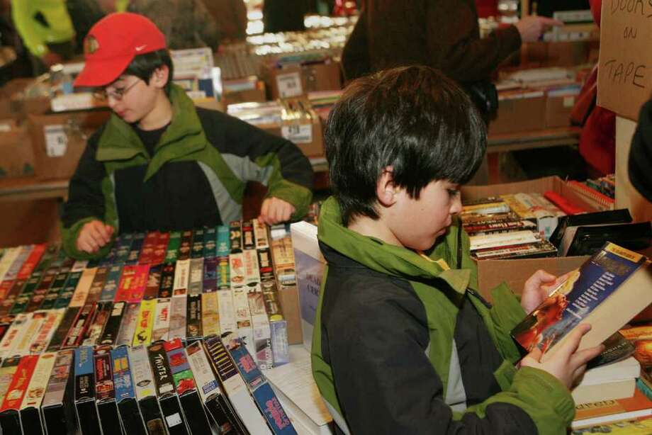 Twins, Sameer, left, and Sanjay  Sadarangani,8, of Southport, search for books  at the Pequot Library annual winter book sale on Sunday, Jan. 16, 2011. The sale runs Monday from 9am-5pm and Tuesday 9am-12pm. Photo: B.K. Angeletti / Connecticut Post