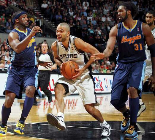 FOR SPORTS - Spurs' Tony Parker looks for room between  Nuggets' Ty Lawson (left) and Nuggets' Nene during first half action Sunday Jan. 16, 2011 at the AT&T Center. Photo: EDWARD A. ORNELAS, SAN ANTONIO EXPRESS-NEWS / eaornelas@express-news.net