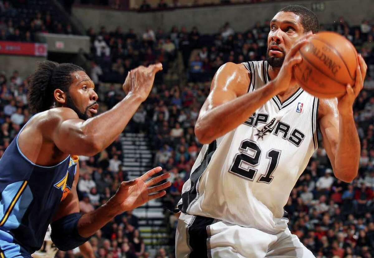 FOR SPORTS - Spurs' Tim Duncan looks for room around Nuggets' Nene during first half action Sunday Jan. 16, 2011 at the AT&T Center.