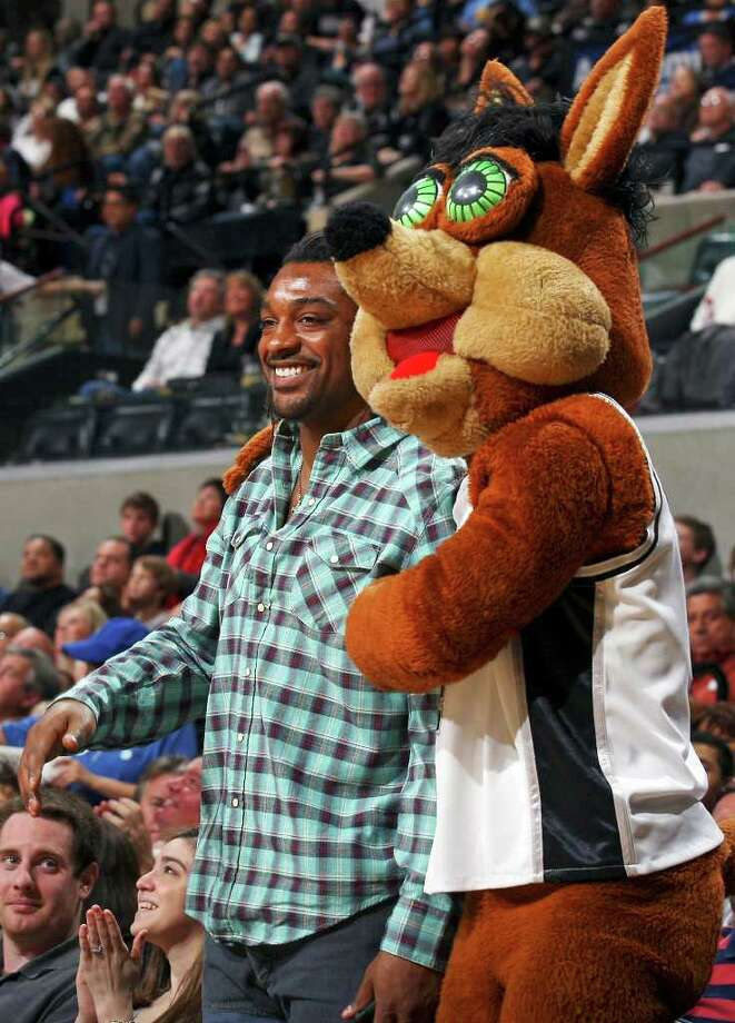 FOR SPORTS - Cedric Benson jokes with the Spurs Coyote during first half action in the game with the Nuggets Sunday Jan. 16, 2011 at the AT&T Center. Photo: EDWARD A. ORNELAS, SAN ANTONIO EXPRESS-NEWS / eaornelas@express-news.net